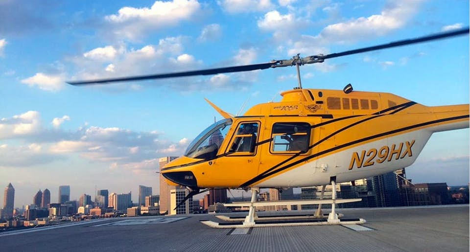 Bell 206-B3 on a helipad with a city background
