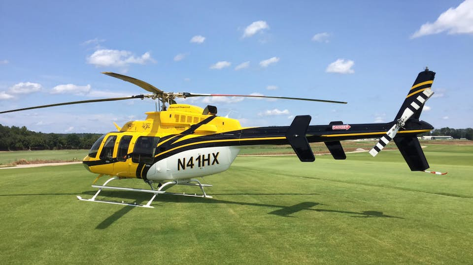 Bell 407HP helicopter in a green field