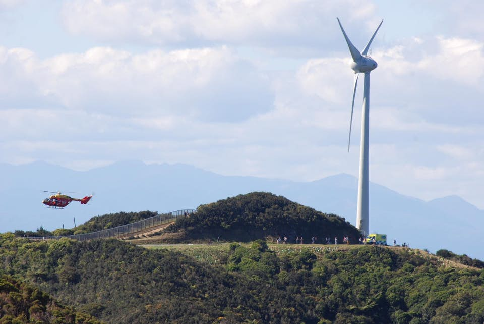 Helicopter flies low near the ground by a land wind turbine