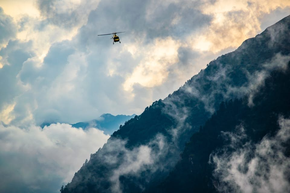 Aerial filming helicopter flying over a mountain through the clouds.