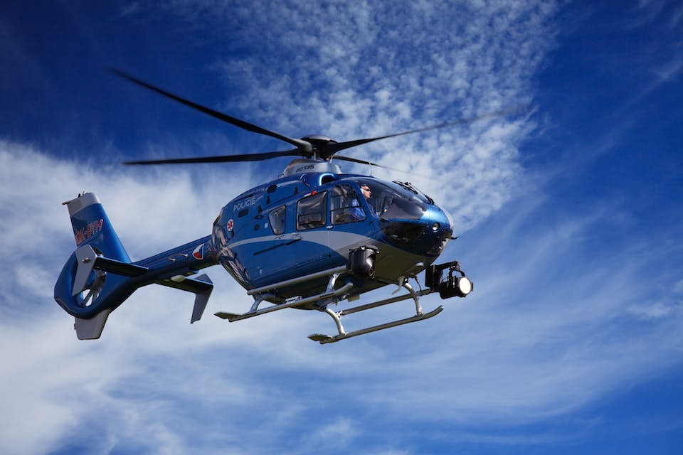Blue helicopter flies in the sky