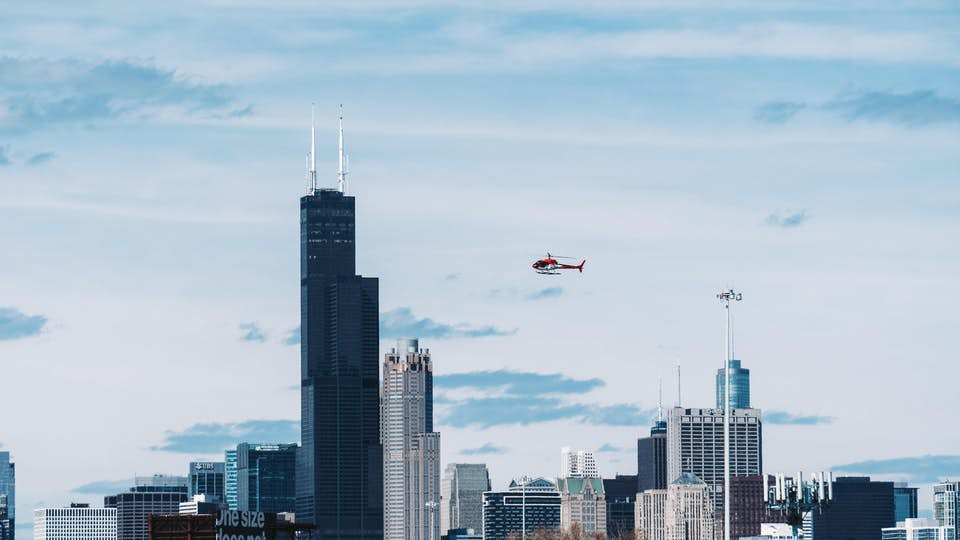 chartered helicopter flies above a city skyline