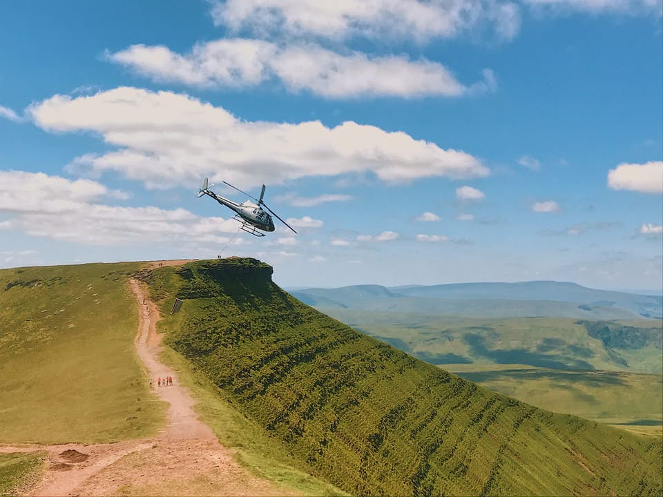 Construction helicopter lifting heavy cargo in mountainous terrain.