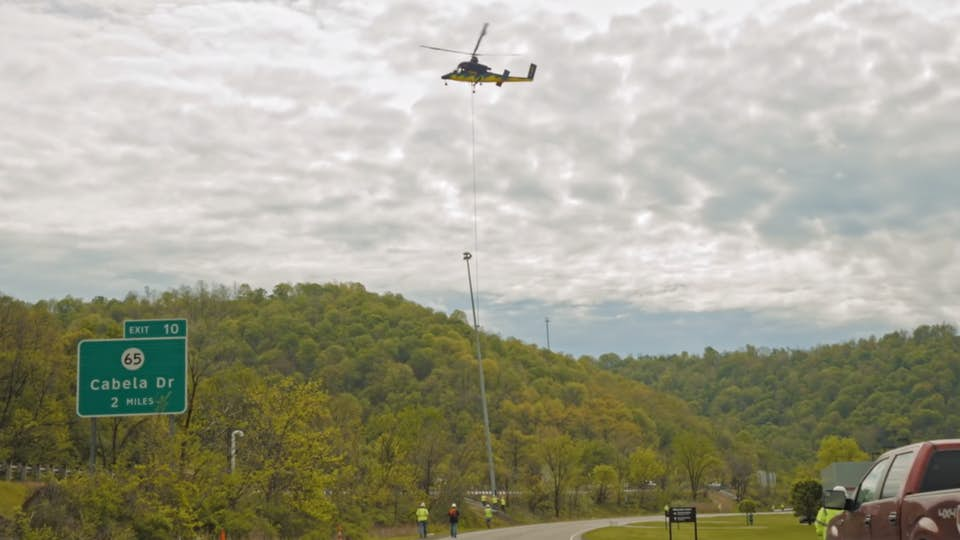 Construction helicopter performing a heavy-lift job over a forest.