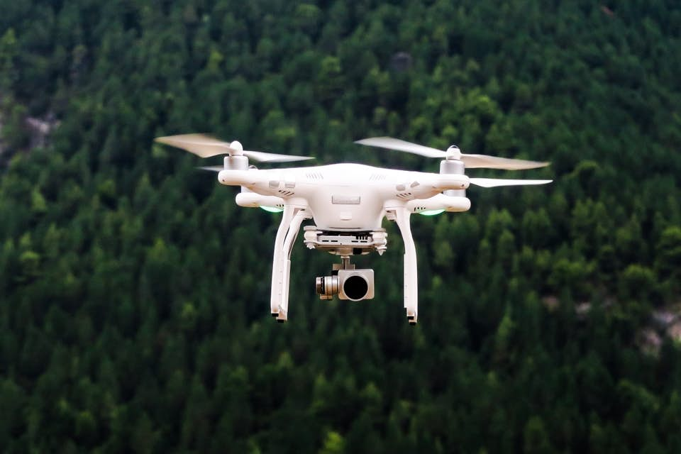 Drone flying over forest capturing aerial photography.