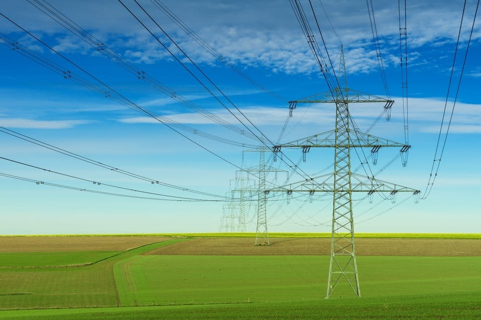 Gray transmission towers under a bright blue sky.