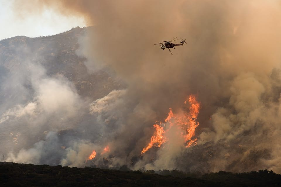 Helicopter flies above smoke and flamed in California wildfire