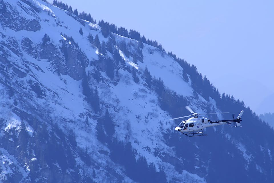 Helicopter flies in front of a snowy mountain