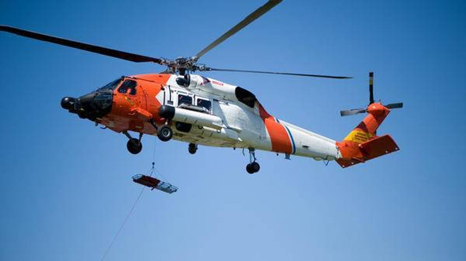 helicopter flies through sky with hoist system