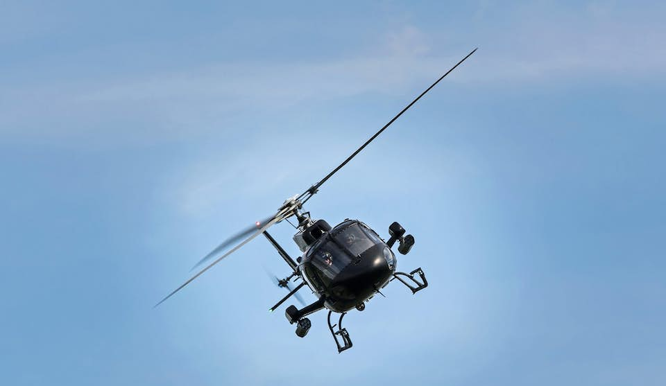 helicopter flying above the ground in the blue sky