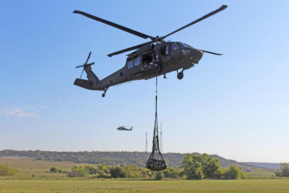 helicopter suspends while carrying cargo net