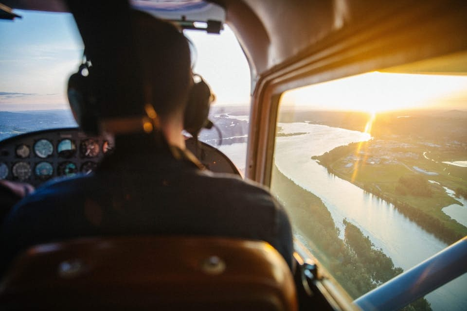 Helicopter pilot flying to a heavy-lift construction site during sunset.