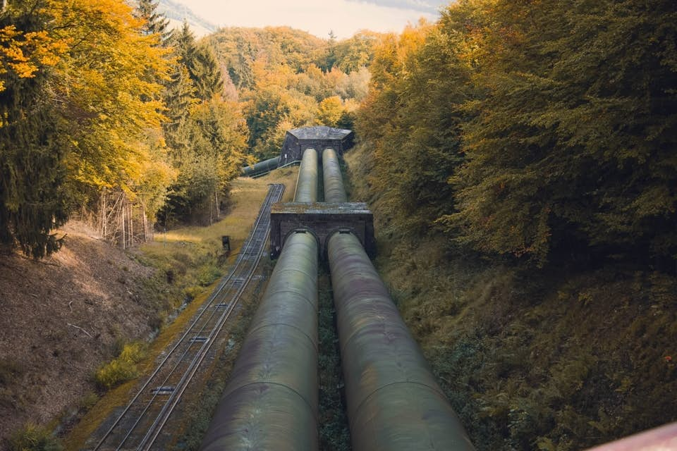 Pipeline laid by aerial crane running through the woods.