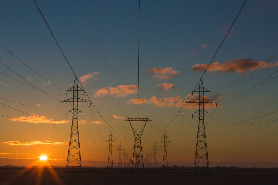 Power lines set by utility helicopter standing tall at sunset.