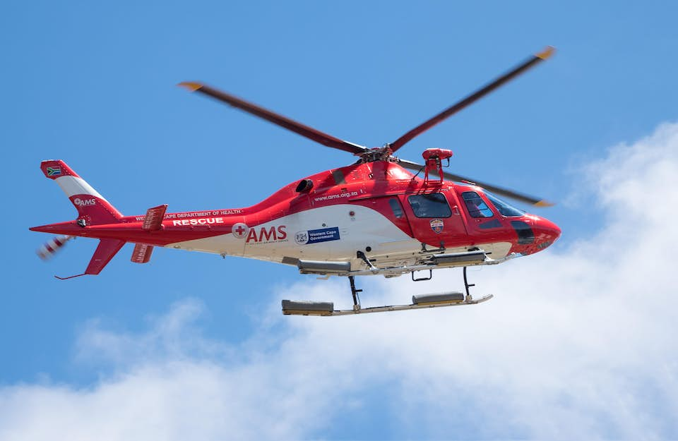 Red rescue and medevac helicopter flies against a blue sky