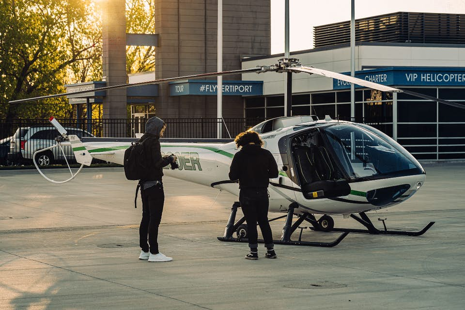 Two chartered helicopter passengers wait on the helipad
