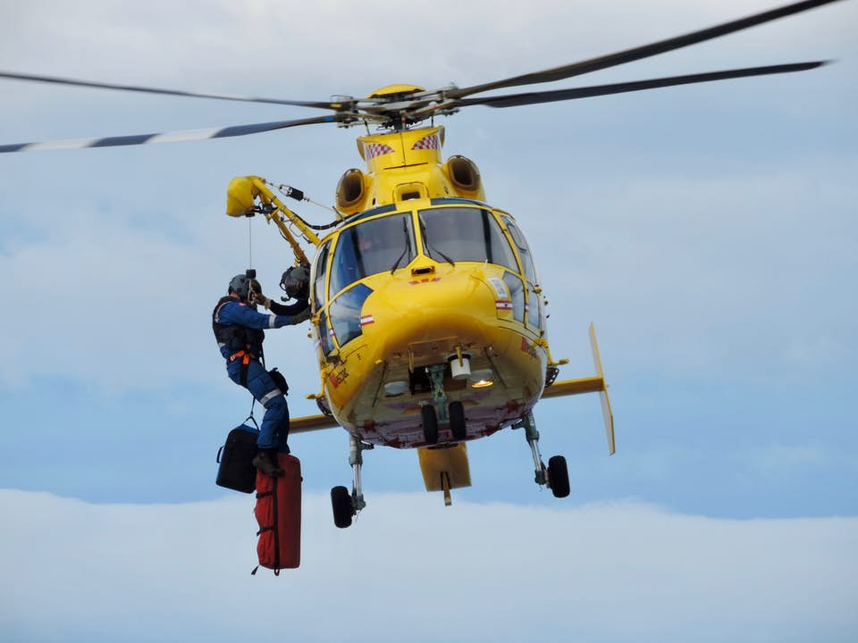 Yellow helicopter performing search and rescue mission with hoist and rappel